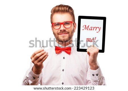 """Studio portrait of young handsome smiling caucasian wearing bowtie man making proposal with wedding ring and tablet pc with words """"Marry me!"""" on it isolated on white background. - stock photo"""