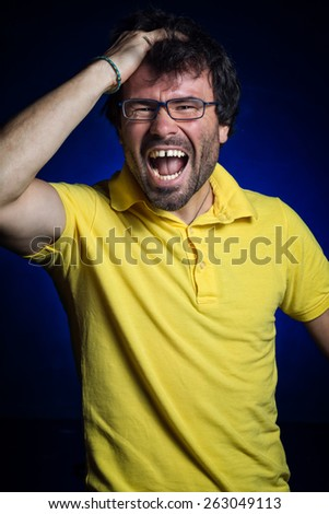 studio portrait of young man shouting to the camera - stock photo