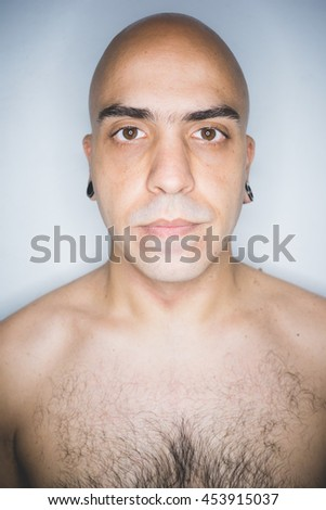 Studio portrait of young mid adult shaved man looking at camera - beard care, wellness concept - stock photo