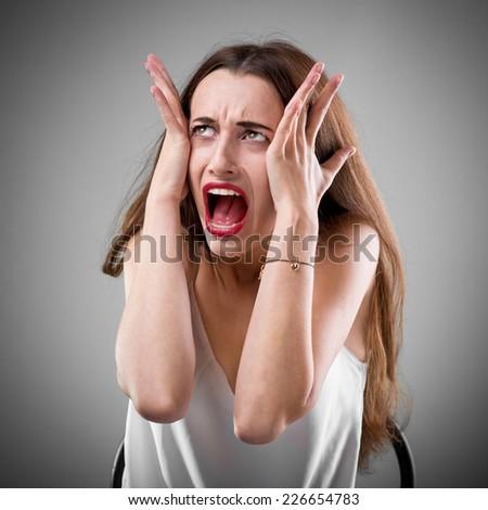 Studio portrait of young yelling woman on grey background - stock photo