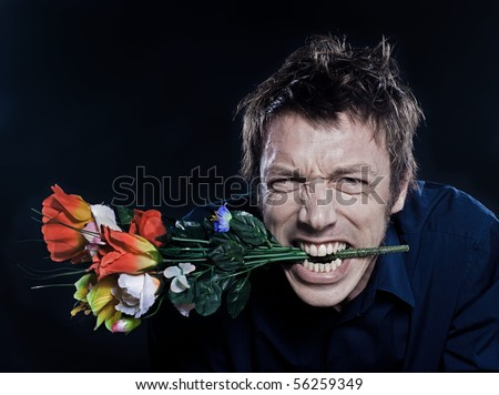 studio portrait on black background of a funny expressive caucasian man offering flowers anger - stock photo