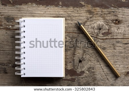 Studio shoot of white notebook and metal pen on wood background - stock photo