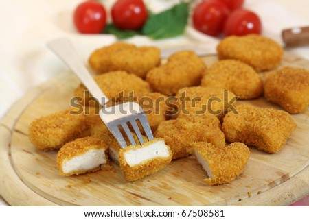 Studio shooting of a fried chicken pieces (nuggets) on wooden desk - stock photo