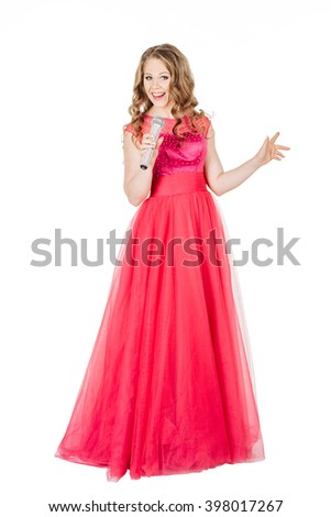 Studio shot beautiful young singing girl in elegant red dress looking at the camera with rhinestone microphone. image on a white studio background. - stock photo