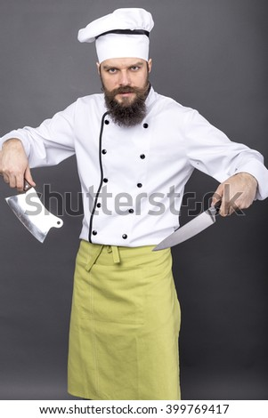 Studio shot of a bearded chef  holding sharp knives over gray background - stock photo