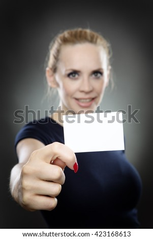 Studio shot of a beautiful business model holding a small business card infront of her.  the business card is in focus and the model is blurred. Shot on a grey background - stock photo