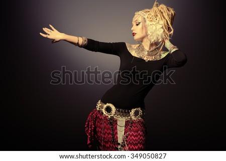 Studio shot of a beautiful traditional female dancer. Ethnic dance. Belly dancing. Tribal dancing. - stock photo