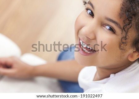 Studio shot of a beautiful young mixed race interracial African American girl child smiling and showing off her perfect white teeth - stock photo