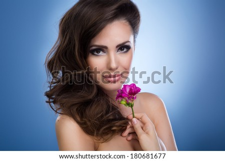 Studio shot of a beautiful young woman holding a flower  - stock photo