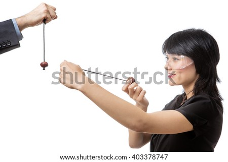Studio shot of a business female wearing protective  playing conkers  - stock photo