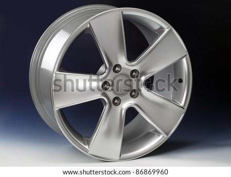 studio shot of a clean glossy aluminum rim in dark blue back - stock photo