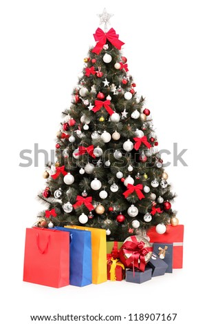 Studio shot of a decorated Christmas tree with gifts and bags isolated on white background - stock photo