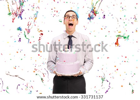 Studio shot of a delighted man holding a birthday cake and looking at the confetti streamers flying around him isolated on white background - stock photo