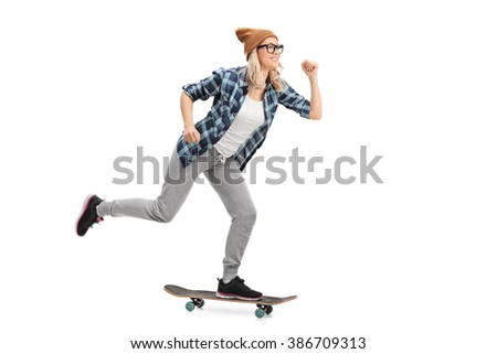 Studio shot of a female hipster riding a skateboard isolated on white background - stock photo