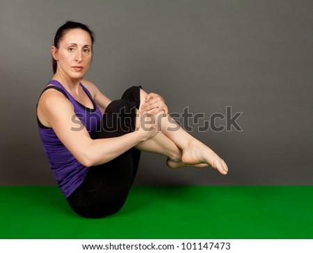 Studio shot of a fit brunette in a paripurna boat yoga pose on a grey background - stock photo