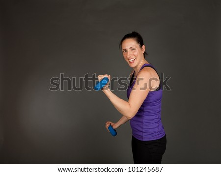 Studio shot of a fit brunette woman lifting weights on a grey background - stock photo