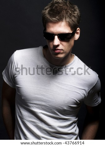 Studio shot of a handsome young male model wearing white T-shirt and sunglasses - stock photo