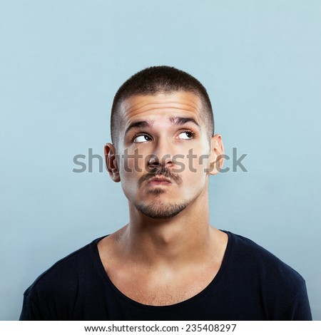 Studio shot of a handsome young man thinking - stock photo