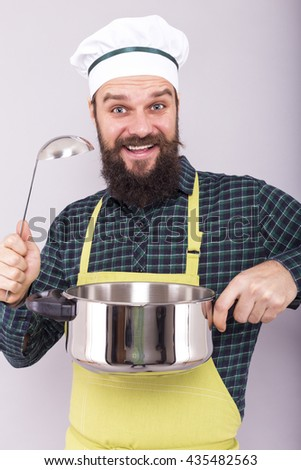 Studio shot of a happy chef holding a pot and ladle  over gray background - stock photo