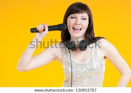 Studio shot of a happy young woman singing with a microphone - stock photo