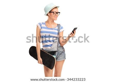 Studio shot of a hipster girl holding a skateboard and listening music on her cell phone isolated on white background - stock photo