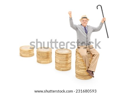 Studio shot of a joyful senior sitting on a pile of coins and holding a cane with the focus on the front pile isolated on white background - stock photo