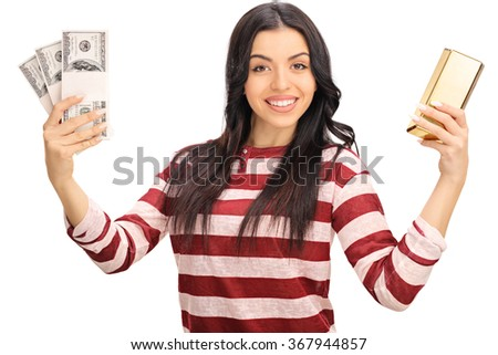 Studio shot of a joyful woman holding a few stacks of money and a gold bar isolated on white background - stock photo