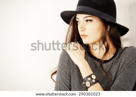 Studio shot of a magnificent young woman in a fitting dress and elegant classic hat. Beauty, fashion concept. - stock photo