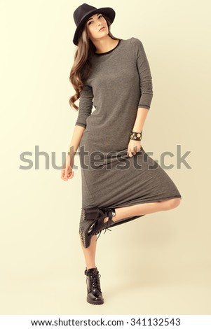 Studio shot of a magnificent young woman in a fitting dress and elegant classic hat. Beauty, fashion concept. Full length portrait.  - stock photo
