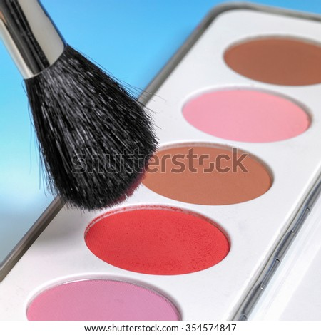 studio shot of a make-up assortment and brush in blue back - stock photo