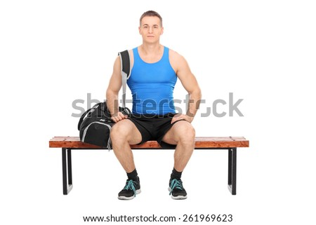 Studio shot of a male athlete in sportswear sitting on a wooden bench and carrying a black sports bag isolated on white background - stock photo