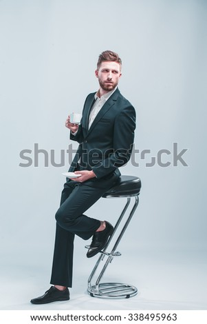 Studio shot of a man with white coffee cup, isolated on gray, sitting on the bar stool - stock photo