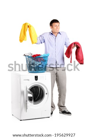 Studio shot of a man wondering how to do the laundry isolated on white background - stock photo