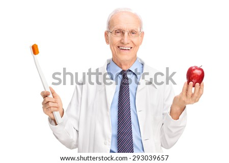 Studio shot of a mature doctor holding a huge toothbrush and a red apple isolated on white background - stock photo