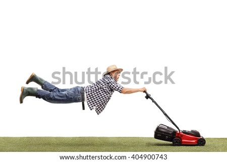 Studio shot of a mature man being pulled by a powerful lawn mower isolated on white background - stock photo