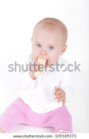 studio shot of a 7 month old baby girl eating a banana - stock photo