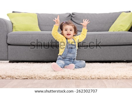 Studio shot of a playful baby girl sitting on the floor next to a modern sofa and gesturing happiness isolated on white background - stock photo