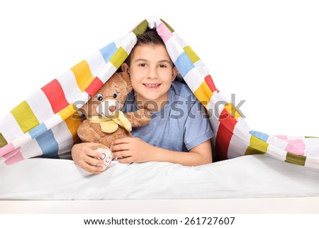 Studio shot of a playful kid holding a teddy bear under a blanket isolated on white background - stock photo