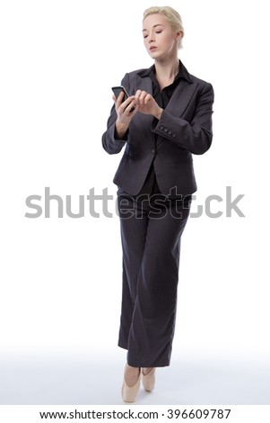 Studio shot of a pretty blonde business model, wearing a suit and ballet shoes, is enpointe whilst holding a mobile phone, isolated on a white background. - stock photo