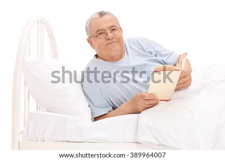 Studio shot of a relaxed senior man lying in bed and holding a book isolated on white background - stock photo