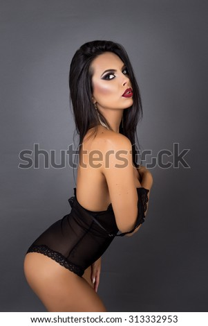 Studio shot of a sensual brunette woman posing in sexy black lingerie over gray background - stock photo