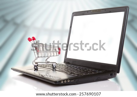Studio shot of a  shopping cart over a laptop computer - stock photo