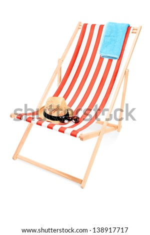 Studio shot of a sun lounger with towel, hat and sunglasses isolated on white background - stock photo