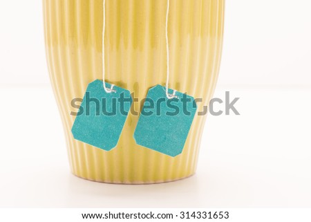 Studio shot of a teacup with two teabags, extra strong tea. Food and drink backdrop showing a mug of hot beverage served.  - stock photo
