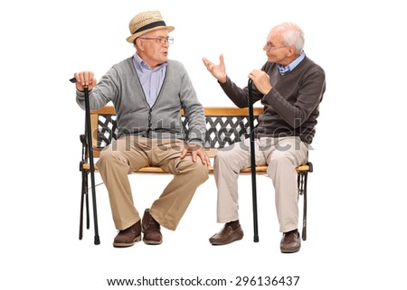Studio shot of a two senior gentlemen having a conversation seated on a wooden bench isolated on white background - stock photo