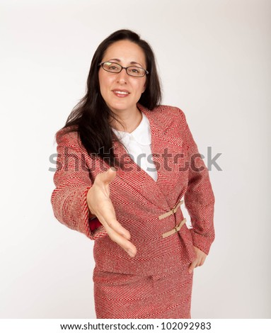 Studio shot of a young businesswoman wearing glasses with an outstretched hand - stock photo