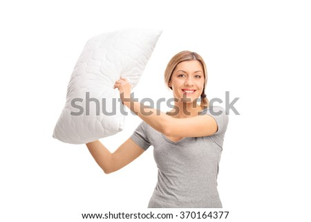 Studio shot of a young cheerful woman having a pillow fight and swinging with a pillow isolated on white background - stock photo