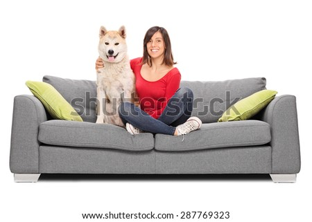 Studio shot of a young girl posing on a gray sofa with her dog and smiling isolated on white background  - stock photo
