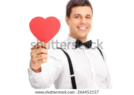 Studio shot of a young guy holding a small heart shaped piece of cardboard and smiling isolated on white background with the focus on the heart - stock photo