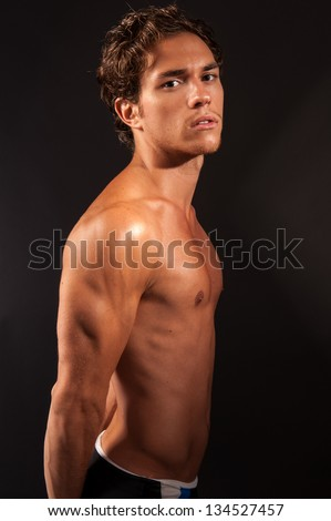 studio shot of a young male with naked torso facing to the side and looking into the camera flexing abdominals and pectoral muscles. - stock photo